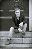 Attractive blue eyed, blond young man sitting on stair steps — ストック写真