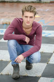 Attractive blue eyed, blond young man sitting on checkered floor — Stock Photo
