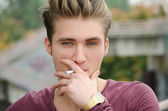 Handsome blond young man smoking cigarette — Stock Photo