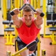 Young man training on gym equipment — Stock Photo