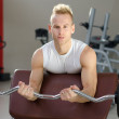 Handsome young man training biceps in gym — Stok fotoğraf