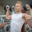 Attractive young man training with dumbbells in gym — Stok fotoğraf
