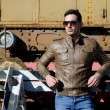 Stock Photo: Attractive young man in leather jacket and jeans in front of old train