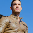 Handsome young man in leather jacket against blue sky — Stock Photo