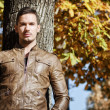 Handsome young man against tree in fall — Stock Photo