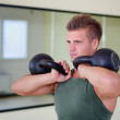 Handsome young man working out in gym with kettlebells — Stock Photo