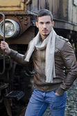 Handsome young man in leather jacket and jeans next to old train — Stockfoto
