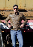 Attractive young man in leather jacket and jeans in front of old train — Stock Photo