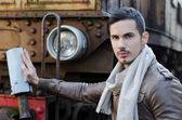 Attractive young man in leather jacket and jeans next to old train — Stock Photo