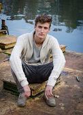 Attraktiv ung man sitter på rostig metall floden — Stockfoto