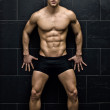 Sexy, muscular young man standing in underwear against dark wall — Stock Photo