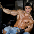 Muscular latino bodybuilder in jeans hanging from metal handle — Stock Photo