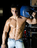 Muscular young man shirtless, carrying gas tank on shoulder — Stock Photo