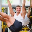 Smiling young man hanging from gym equipment — Stock Photo