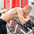 Young man resting on dumbbells rack after workout in gym — Stock fotografie