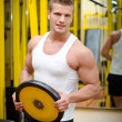 Handsome young man in gym holding weight — Stock Photo
