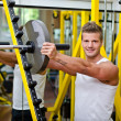 Smiling young man in gym putting weight disc on barbell — Stock Photo