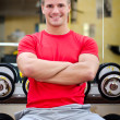 Handsome smiling young man in gym sitting on dumbbells rack — Stock Photo