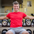 Handsome smiling young man in gym sitting on dumbbells rack — Stock Photo #36867041
