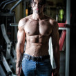 Shirtless muscular man in gym holding weights — Lizenzfreies Foto