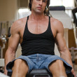 Stock Photo: Bodybuilder in gym working out on legs machine