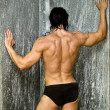 Back of muscular man in shower — Stock Photo