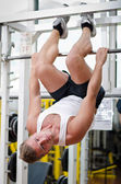 Young man in gym hanging upside-down to exercise abs — Stock Photo