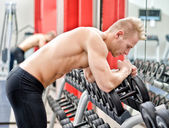 Young man resting on dumbbells rack after workout in gym — Stock Photo