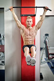 Young man hanging from gym equipment — Stock Photo