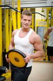 Handsome young man in gym holding weight — Stok fotoğraf
