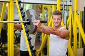 Sonriente a joven en gimnasio poniendo disco peso en barra — Foto de Stock