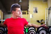 Handsome young man in gym sitting on dumbbells rack — Stock Photo