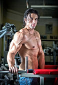 Handsome shirtless muscular man with jeans in gym — Stock Photo
