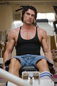 Bodybuilder in gym working out on legs machine — Stock Photo