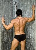 Achterkant van gespierde man in douche — Stockfoto