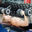 Stock Photo: Muscular young mshirtless, training pecs on gym bench