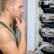 Confused male electrician in front of power panel — Stock Photo