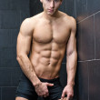 Handsome, muscular young man shirtless leaning against tiled wall — Stock Photo