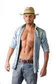 Trendy young man with jeans, open denim shirt and straw hat — Stock Photo