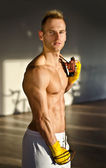 Shirtless muscular young man standing with jumping rope in gym — Stock fotografie