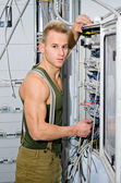 Handsome male electrician in front of power panel — Stock Photo