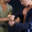 One man putting handcuffs to another man — Stock Photo