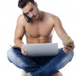 图库照片: Shirtless young moverwhelmed by technology: PC, tablet, phones