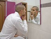 Handsome young man looking at himself in bathroom mirror — Stock Photo