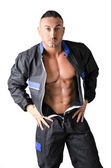 Bodybuilder mechanic opening coverall to show muscular body — Stock Photo