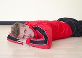 Joven atractivo tirado en el piso con traje de gimnasio — Foto de Stock