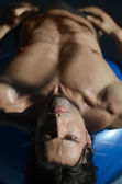 Muscular shirtless man laying down, belly up — Stock Photo