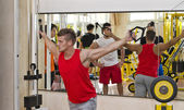 Young man training pecs on gym equipment — ストック写真