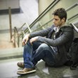 Handsome young man sitting on stairs — Stock Photo #40292031