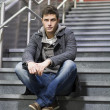 Handsome young man sitting on stairs — Stock fotografie